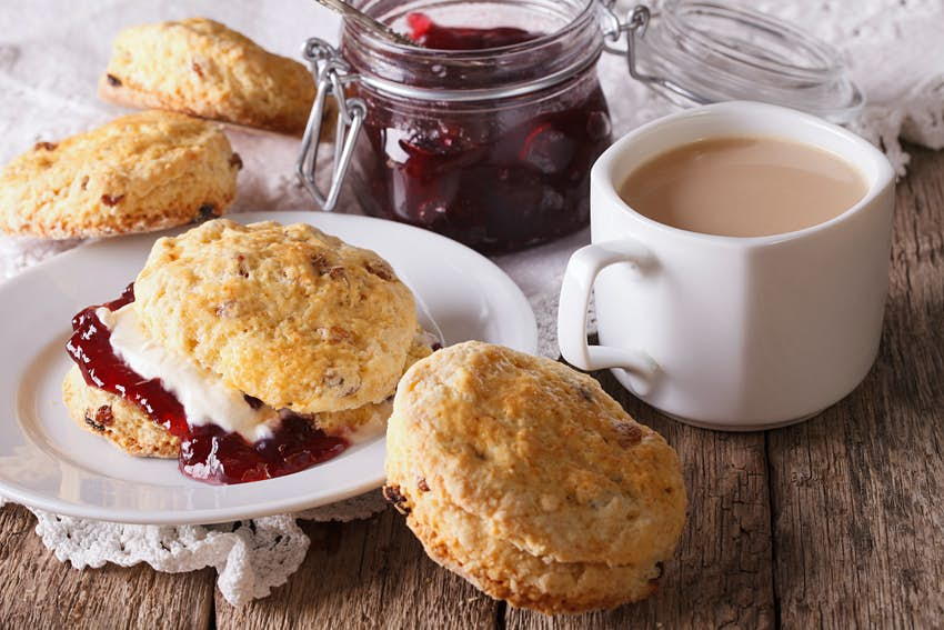 Scones with jam and tea with milk close-up on the table
