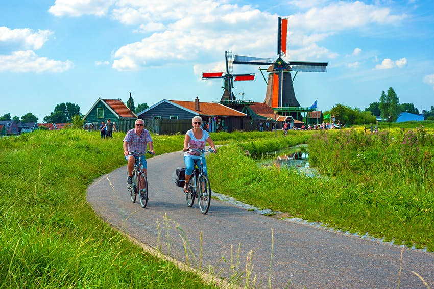 Two cyclists ride bikes on a path surrounded by grassland. There are windmills in the background