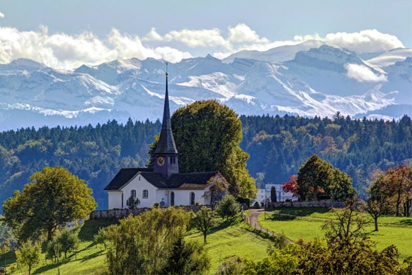 A church in the middle of a green field, in the background are the snow-capped Alps