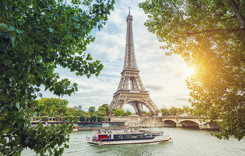 A river boat passes in front of the Eiffel Tower.