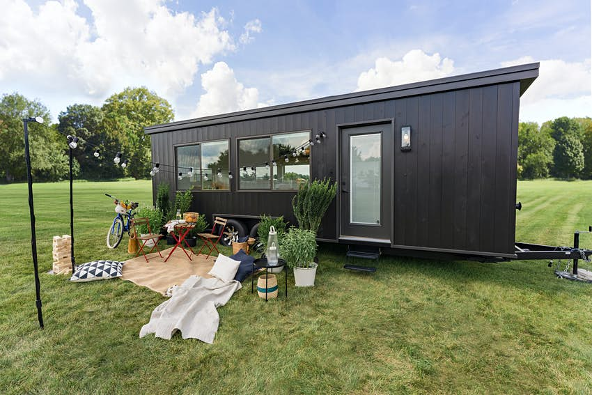 Exterior shot of a panel-clad tiny home in a field with a picnic space outside