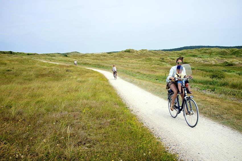 Family cycling through sand dunes in Vlieland, Netherlands