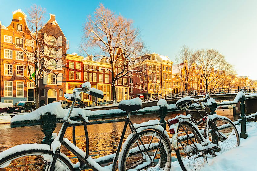 Bicycles lined up near a railing by a canal. They are all covered in snow.