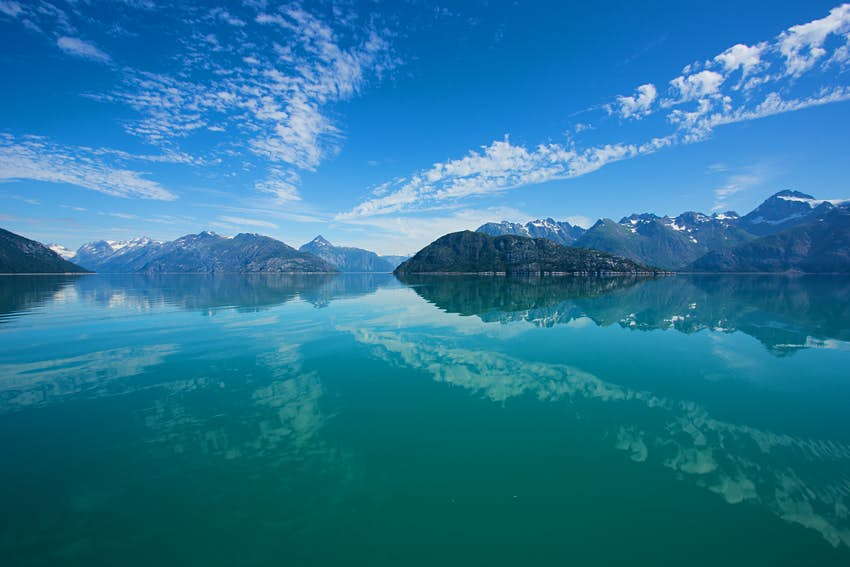 Snow-capped mountains reflected in still waters at Glacier Bay National Park.