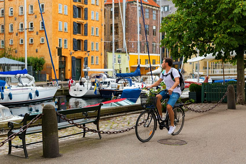 A cyclist passes a canal lined with small boats.