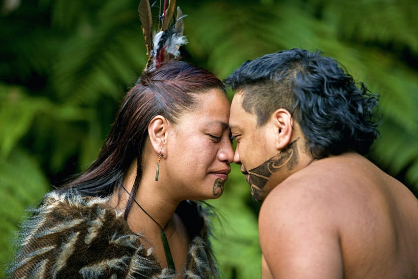 A couple touch heads during a Maori hongi greeting