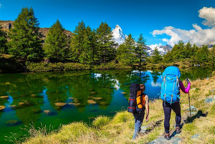 Hai người đi bộ đường dài với ba lô gần hồ núi cao Grindjisee ở Zermatt