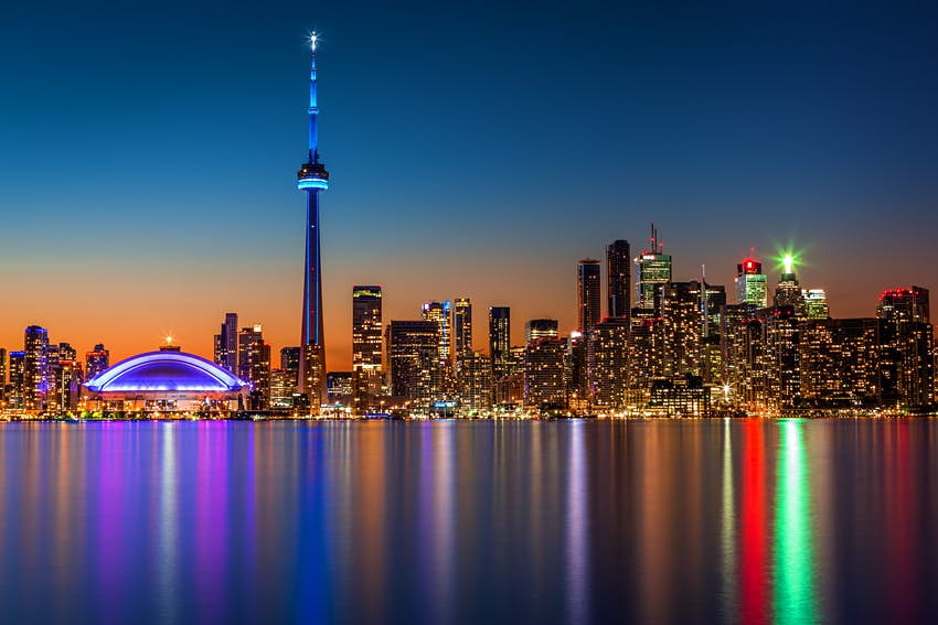 The Toronto skyline at dusk, with a tall needle-like building dominating the shot. Lights are reflected on the water.