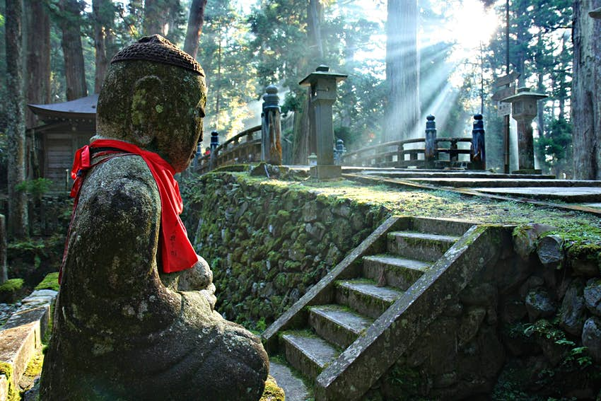 A stone Buddha with a red ribbon around its neck. It is set in forest with beams of sunlight shining between the trees.