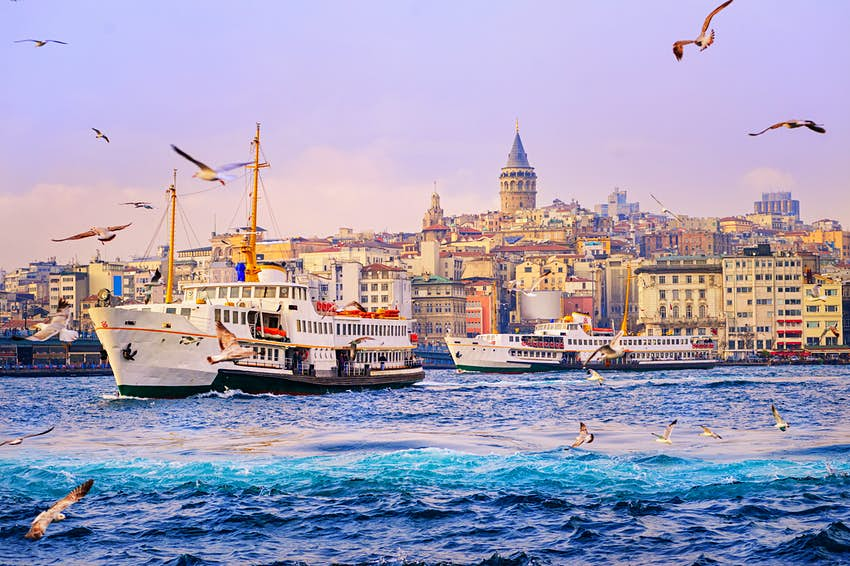 Birds circle a ferry leaving Golden Horn in Istanbul, Turkey