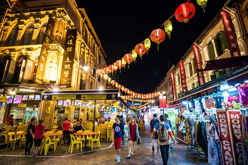 The Chinatown district in Singapore with diners sat on yellow plastic chairs and tables outside restaurants at night with lanterns hanging across the street lit up.