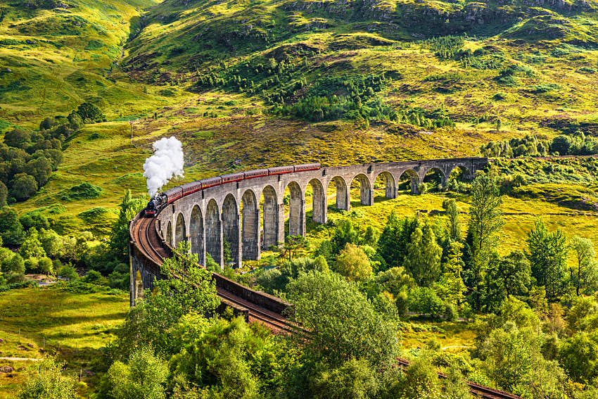 A viaduct with many arches rises above green hillsides. A steam train chugs along it.