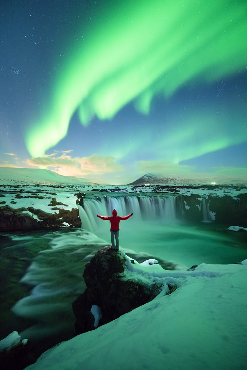 A man stands in the darkness with the northern lights shining above.