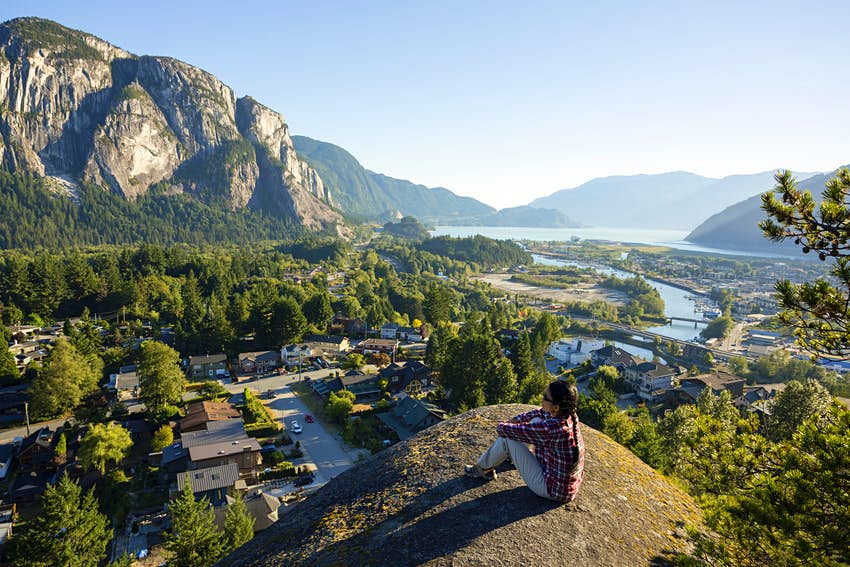 Woman sitting on the edge of a cliff at Smoke Bluffs Park overlooking Howe Sound and the Stawamus Chief in Squamish.
