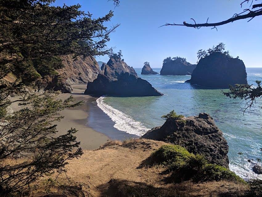 Rocky sea stacks and crumbling volcanic bluffs rise up from a crescent shaped beach and blue waves