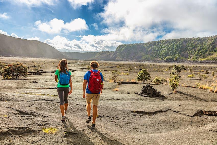 Hiking couple walking on Kilauea Iki crater trail on Big Island