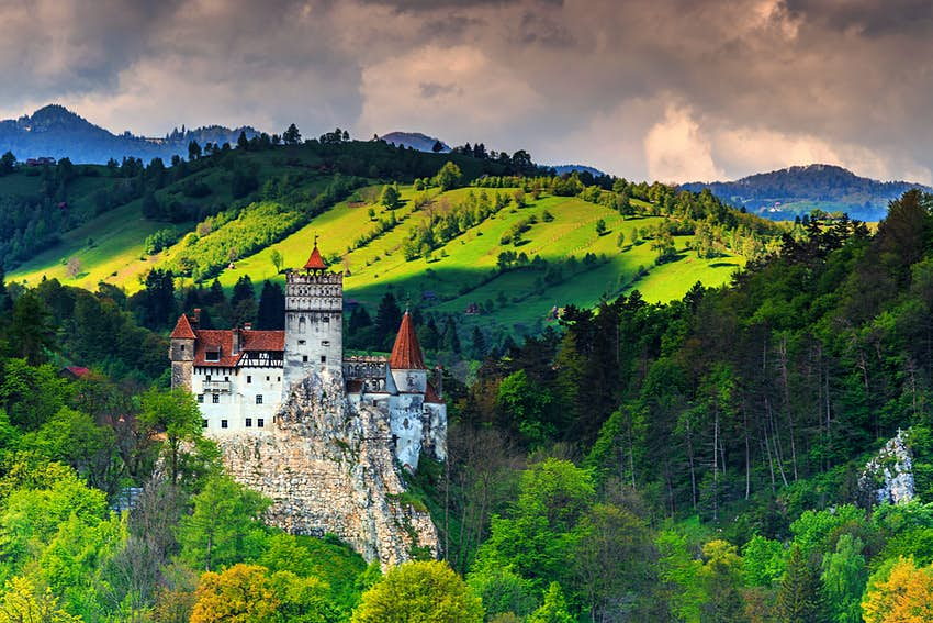 A castle on a hill stands in front of a lush mountainous area.