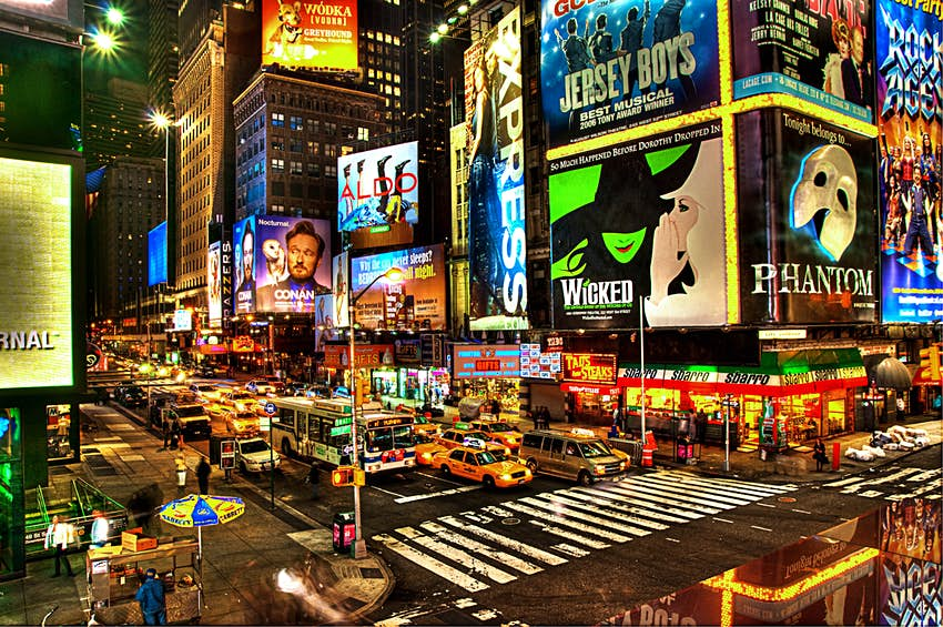 Broadway traffic and neon signs shine during dusk in New York City