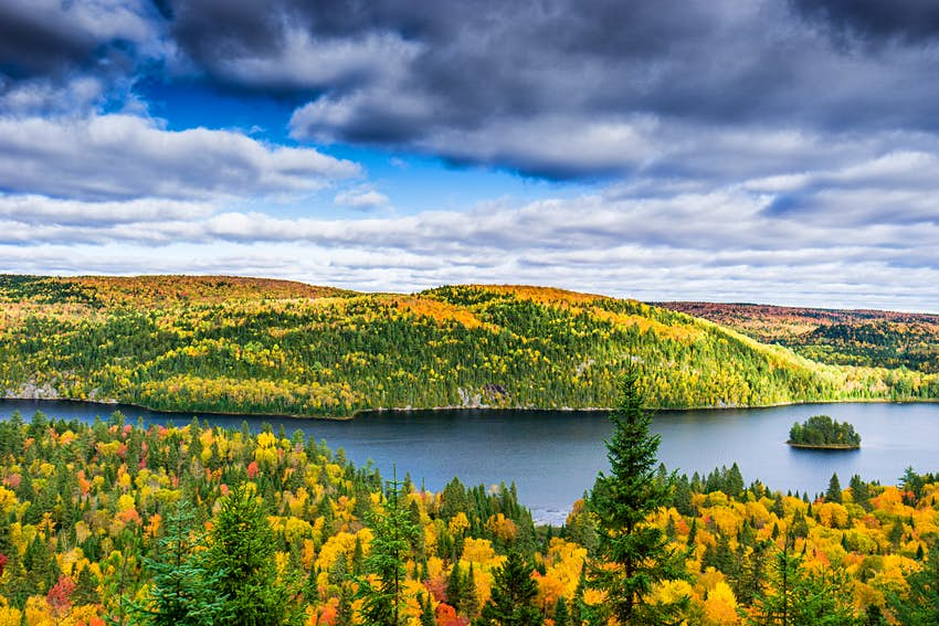 Autumn colors around a lake with cloudy skies over head