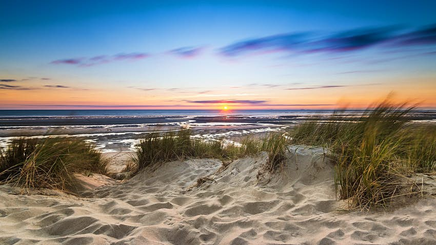 Sand dunes at the edge of a body of water with the setting sun