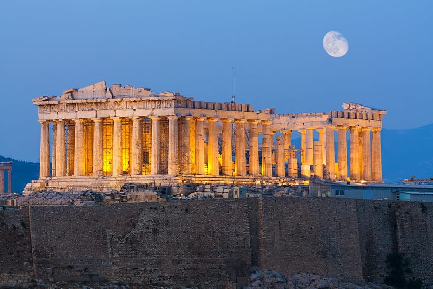 Parthenon construction on Acropolis Hill in Athens during the early evening with the moon in the sky.