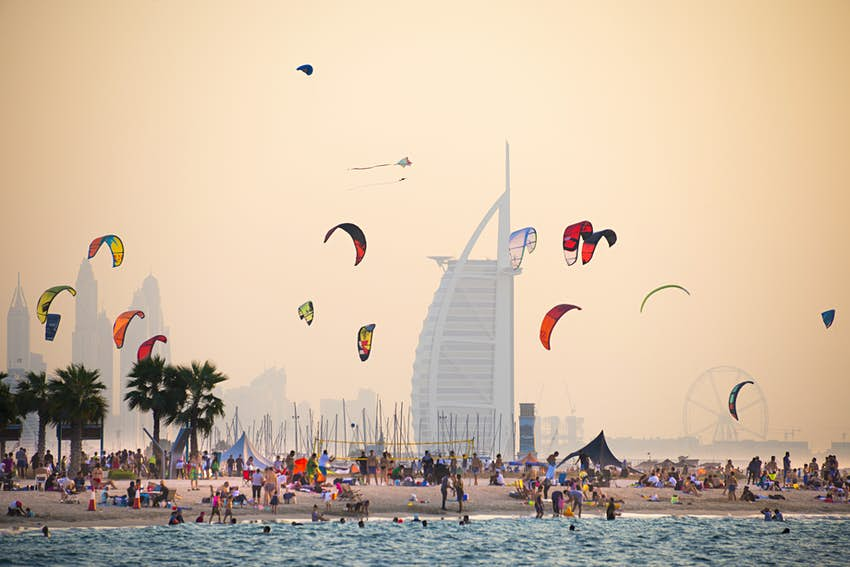 A kite beach full of kite surfers in Jumeirah with the Burj Al Arab in the background.