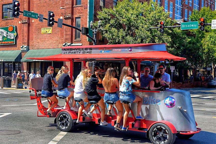 Nashville, TN, USA - September 21, 2019:  Revelers enjoy drinks on a Sprocket Rocket pedal bike tavern on Broadway Street.  These vehicles are powered