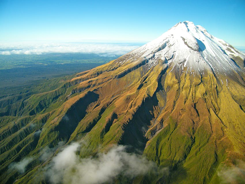 Green bush leads up to a snow-capped top of Mt. Taranaki in Egmont in New Zealand