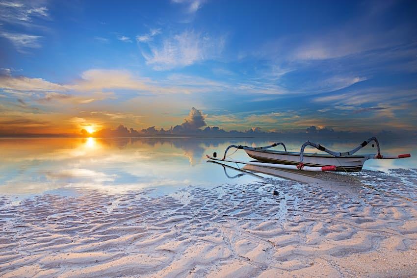 Boat on white sands of Sanur beach at sunrise