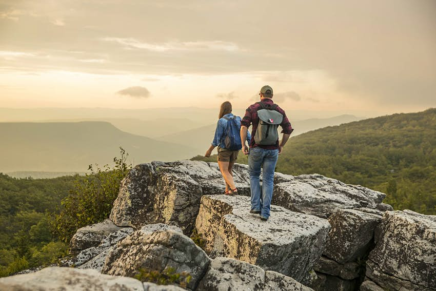 A man and woman hiking over rocks in West Virginia