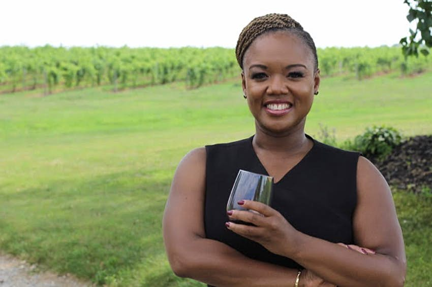 A woman wearing a black dress smiles at the camera while holding a glass of wine. In the background is a grape vineyard.