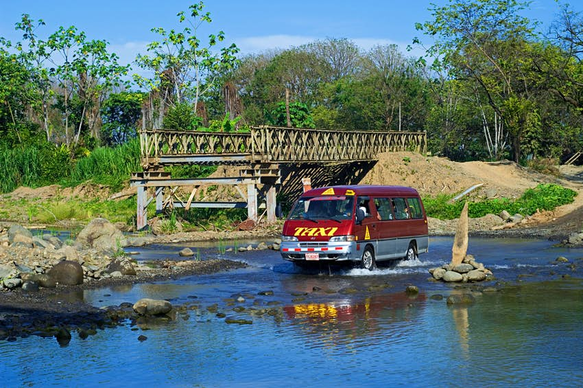 Taxi crossing river by driving through water next to unfinished bridge in Costa Rica