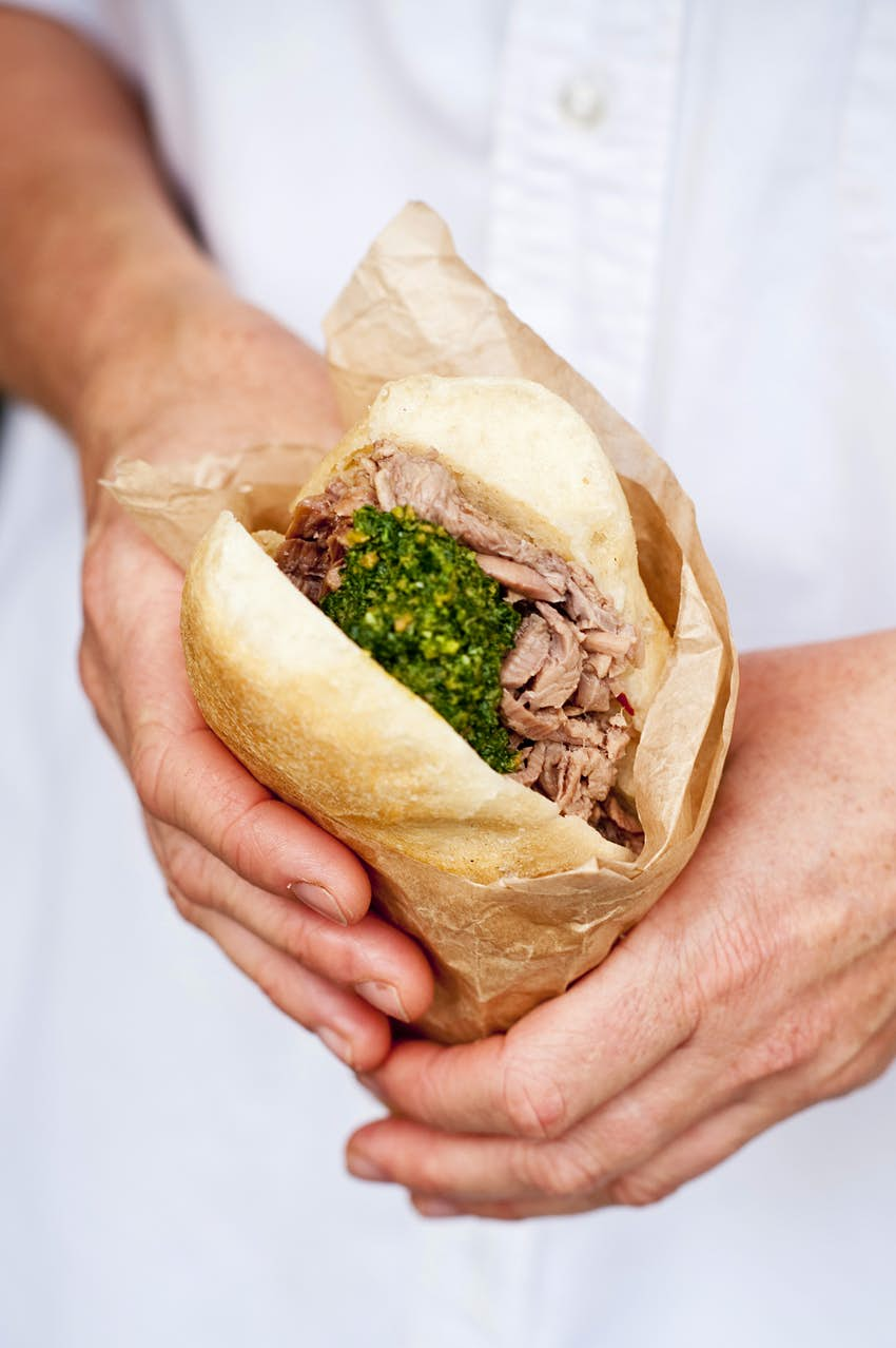 A panino (type of sandwich bread) stuffed with offal and a garnish of green herbs