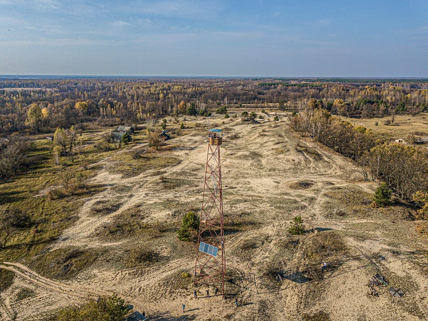A firetower stands with Chernobyl somewhere in distance.