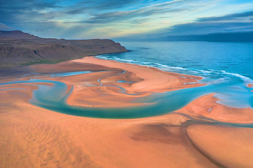 Aerial drone view of azure water streams and reddish-yellow sand