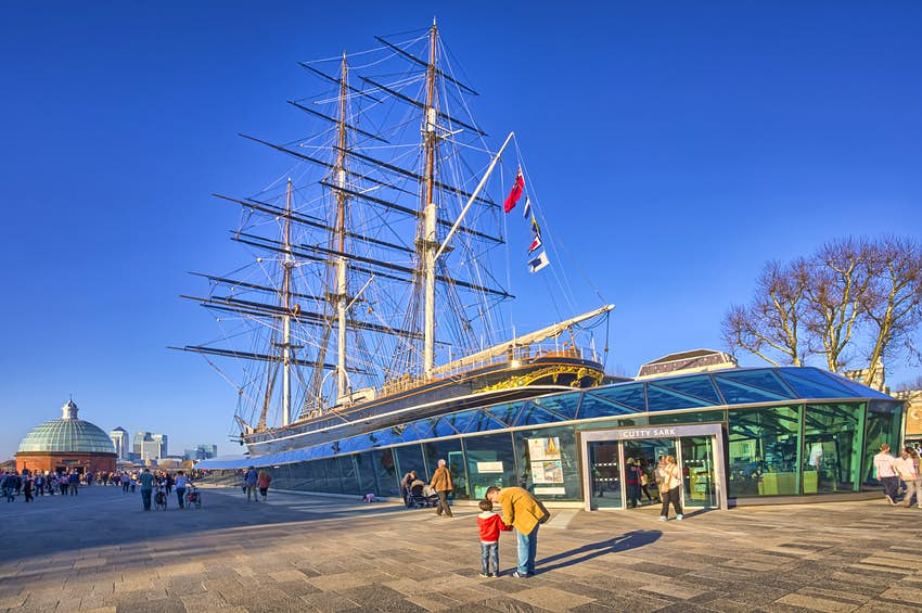 A tea clipper boat on land surrounded by glass to form a museum building. A man kneels down next to a child in the foreground, pointing upwards at the boat's masts.