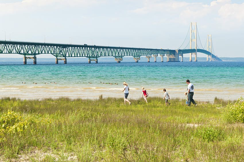 Mackinac Bridge with Family on Grassy Shore