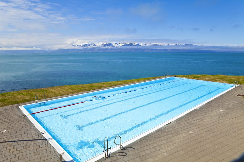 A bright-blue swimming pool on the edge of the sea, providing an infinity pool vibe