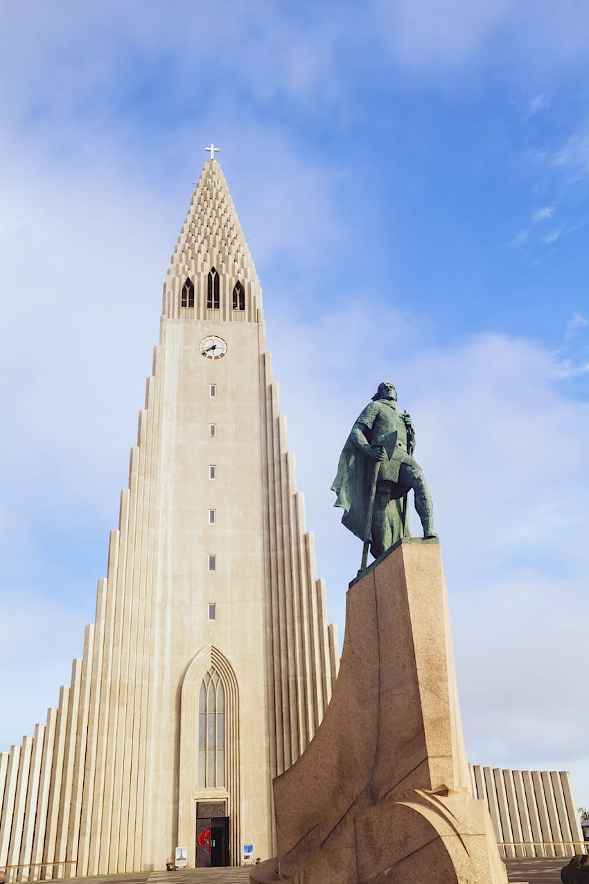 A huge white concrete church photographed against a blue sky. In front of the church is a statue of a man on a plinth
