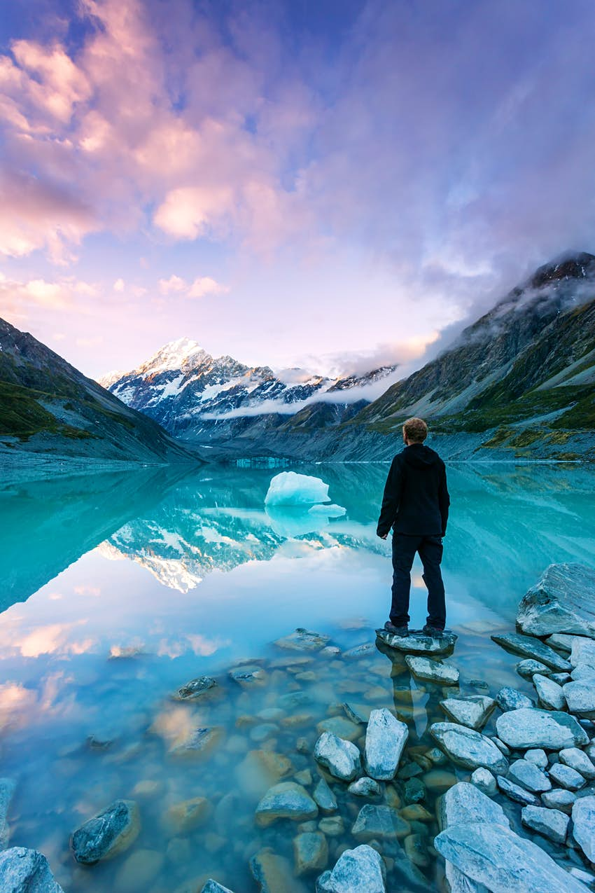 Hiker looks at Mt Cook from a crystal clear lake with an iceberg in New Zealand