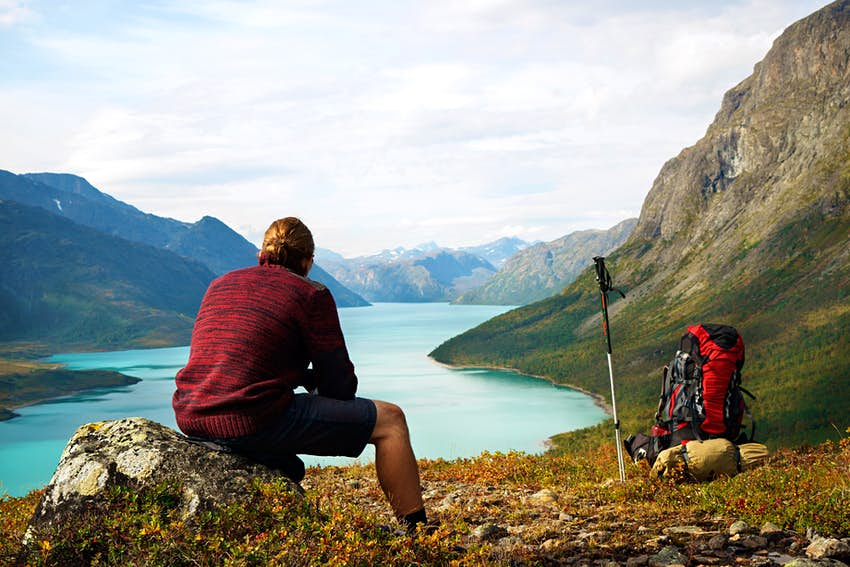 Hiker looking at scenic view of Lake Gjende in the Jotunheimen National Park, Norway