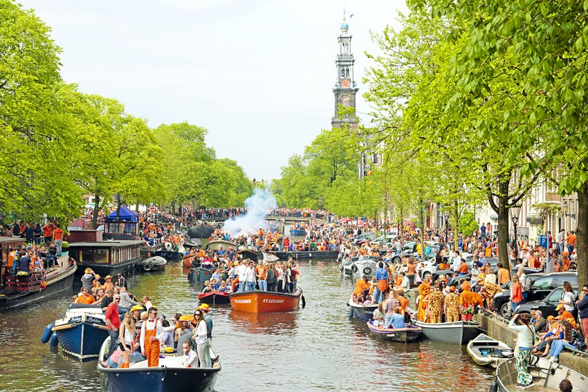 Amsterdam canals full of boats with people dressed in orange to celebrate King's Day