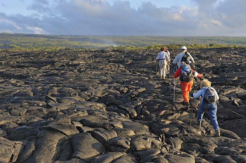 Group of hikers walking on cooled pahoehoe lava flow at sunrise, Kilauea Volcano, Big Island, Hawaii Islands, USA