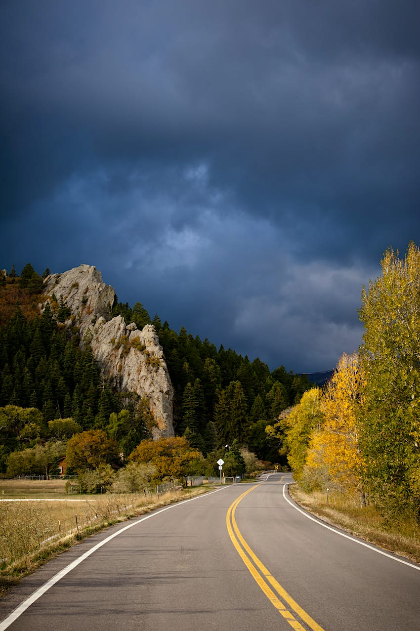 Highway with trees in fall color and stormy sky.  Walsenburg, Colorado.