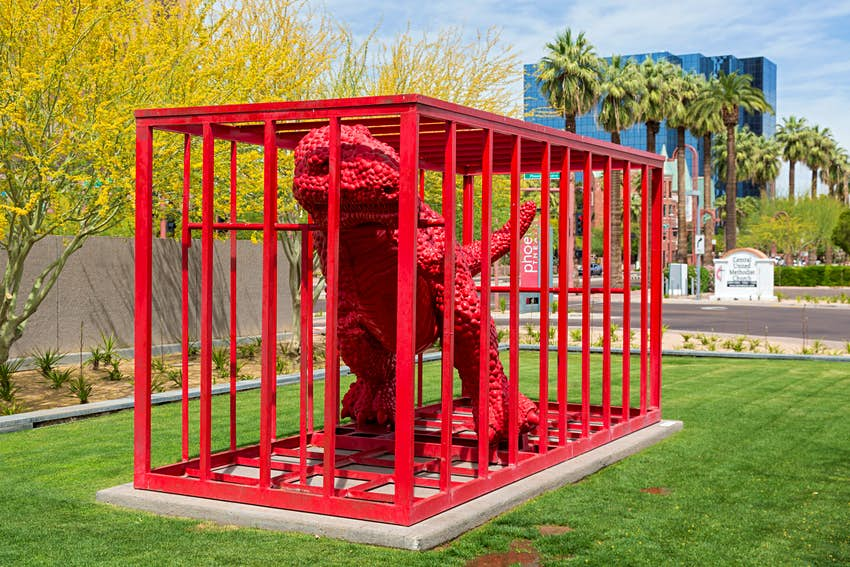 Phoenix, Arizona - A red dinosaur in a red cage at the Phoenix Art Museum.