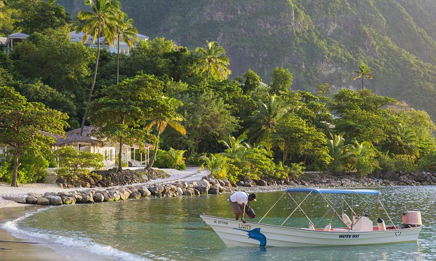 View along Jalousie Beach at sunset, water taxi in foreground, Soufriere, St Lucia