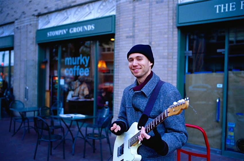 A man smiles and strums an electric guitar