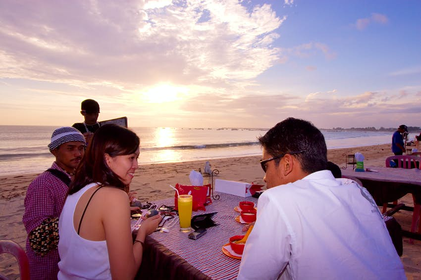 People sit around a table with a meal on the sand at sunset