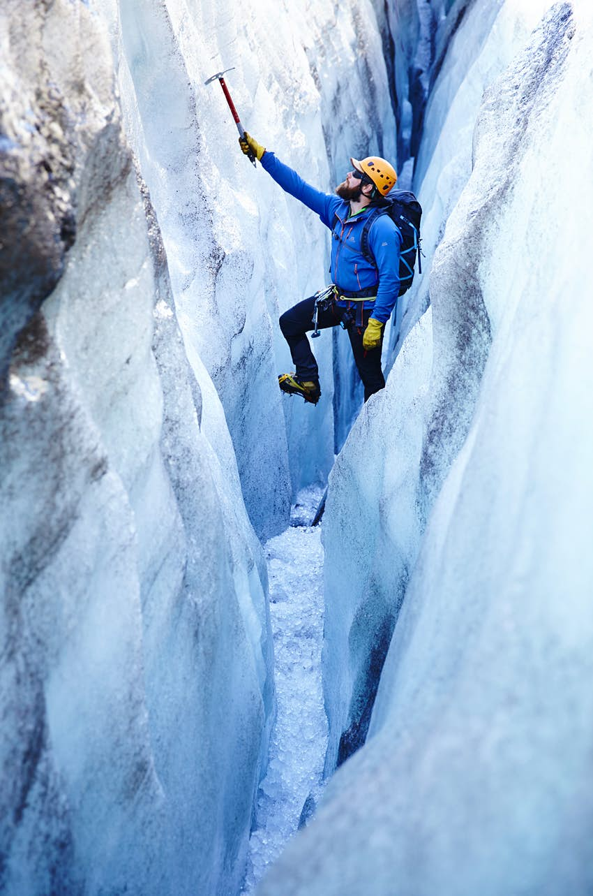 A man in climbing gear hangs off an ice-pick in an icy crevasse