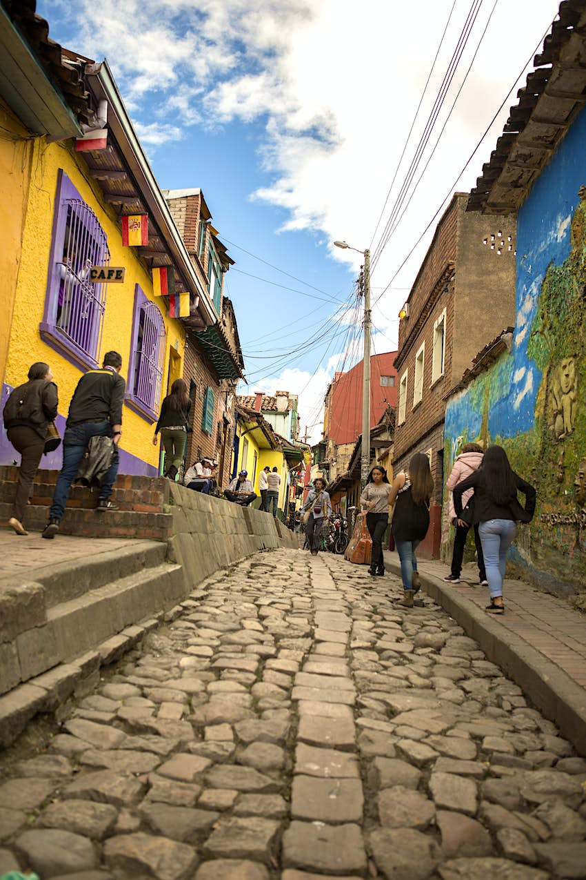 People walk down a cobble stoned alleyway with colorful buildings on either side